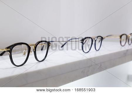 detail view of various eyeglasses lying on a tray.
