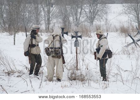 LENINGRAD REGION, RUSSIA - JANUARY 15, 2017: German soldiers during the Second world war on the cemetery field.Fragment of military-historical reconstruction on the liberation of Leningrad