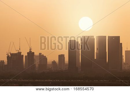 Silhouette buildings in Bangkok Thailand in morning with sun on warm orange sky. Traffic jam on tollway road on shadow.