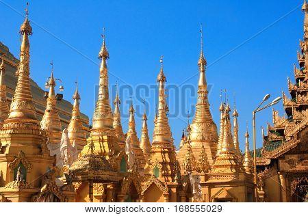 Golden stupas in Shwedagon Zedi Daw (Great Dagon Pagoda, Golden Pagoda), Yangon, Myanmar. On blue sky background