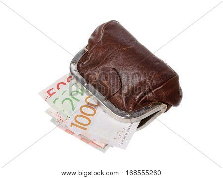 One open brown purse with Swedish banknotes inside in different denominations isolated on white background.