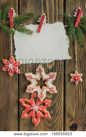 Christmas gingerbread cookies hanging with blank sheet of paper on rope on wooden background.