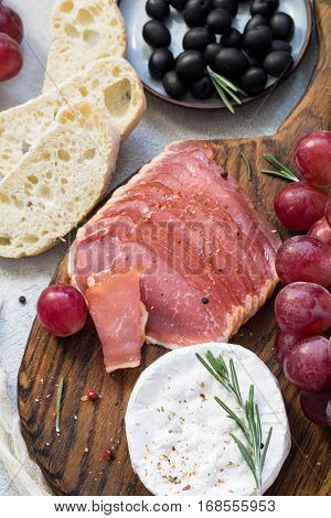 Italian appetizer plate: cured meat, cheese, grapes, olives and fresh bread. Top view