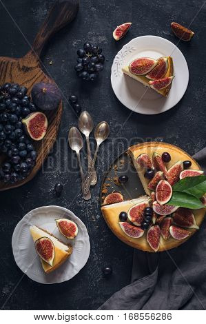 Cheesecake decorated with fresh fruits (figs and grapes). Top view, flat lay. Food still life