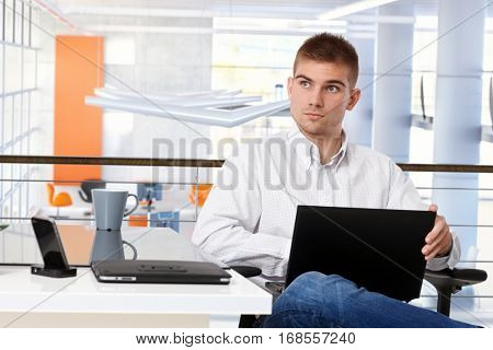 Young casual creative businessman with laptop at business office desk, sitting, thinking.