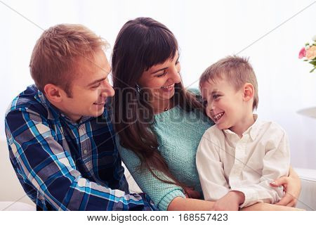 Close-up of happy family. Loving mother and father looking at their smiling child. Sitting on the sofa and posing at the camera