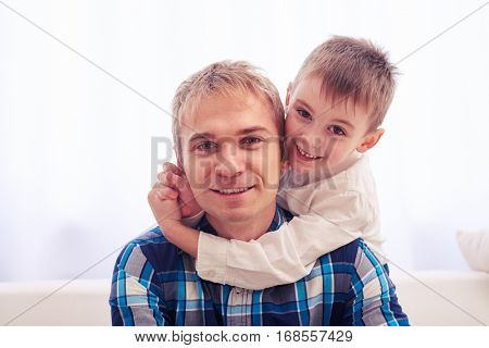 Close-up of joyful father and son. Heartwarming hugs. Little son hugs his father on head.Sitting on the sofa and posing at the camera