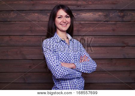 Mid shot of exhilarating woman posing with folded arms. Looking at the camera. Beautiful long-haired girl wearing nice well-combined outfit