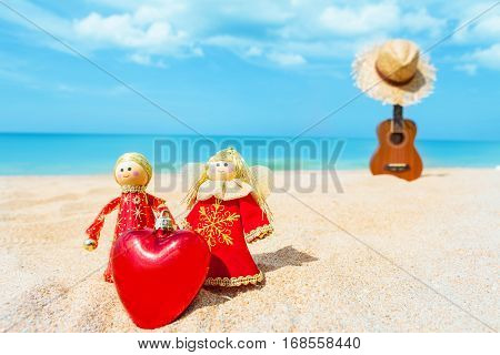 two Christmas doll an angel give a Heart on the sand beach and blue sky summer with Ukulele and hat