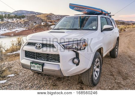 FORT COLLINS, CO, DECEMBER 30, 2016: Toyota 4Runner SUV (2016 Trail edition) carrying  a stand up paddleboard on shore of Horsetooth Reservoir