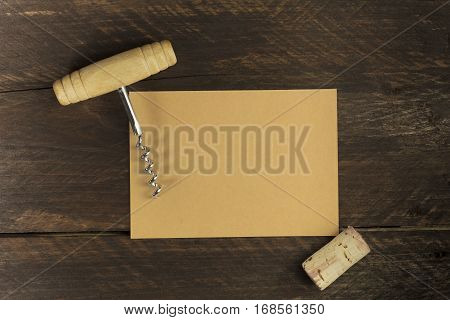 Photo of old-fashioned corkscrew with a cork, shot from above on dark brown background texture with a piece of brown kraft paper for copy space. Design template for wine list or tasting invitation