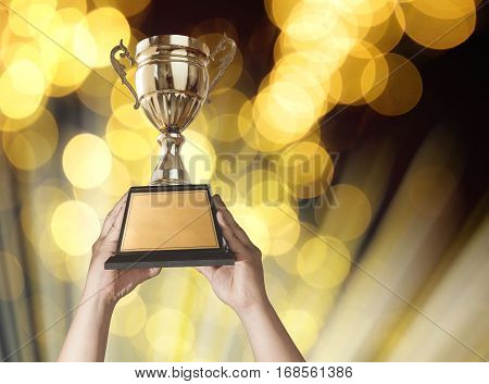 A Man Holding Up A Gold Trophy Cup With Bastract Gold Light Bokeh Background Copy Space Ready For Yo