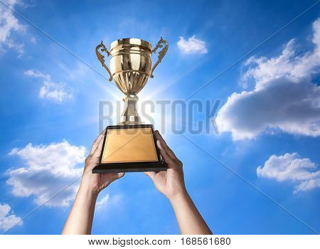A Man Holding Up A Gold Trophy Cup With Bluse Sky And Sun Background Copy Space Ready For Your Troph