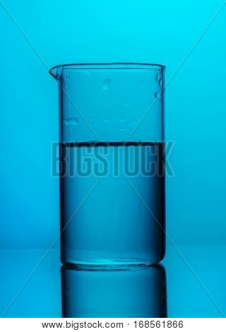Chemical flask with liquid on blue background