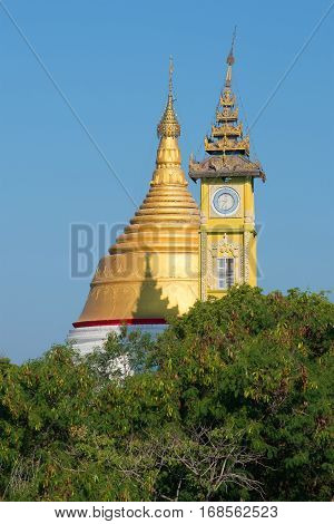 Buddhist stupa and the clock tower on top of the mountain. Sagaing, Myanmar