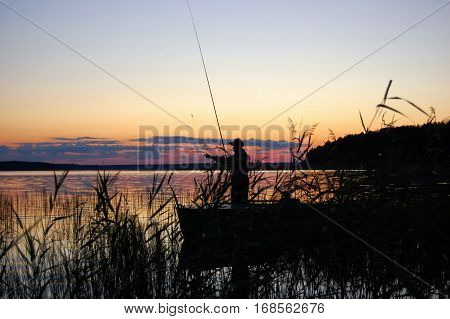 Fishing at sunset. Fisherman holding a fishing rod vertically. Reed stands in the foreground.