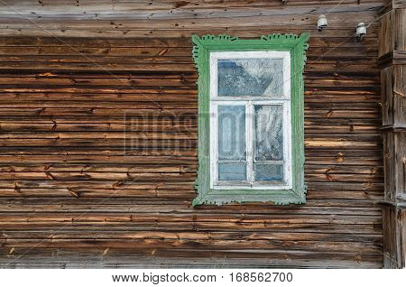 Fragment of a wall of the village houses. Wall covered with boards. The window has a green casing.