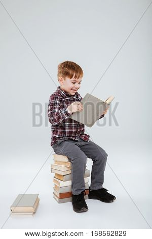 Vertical image of happy young boy in shirt reading book and sitting on books. Isolated gray background