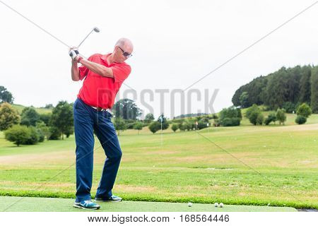 Golfer training his swing on golf driving range