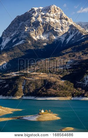 Serre Poncon Lake and Saint Michel Chapel in the Southern French Alps. The peak of Grand Morgon rises above Saint Michel Bay. Hautes Alpes France