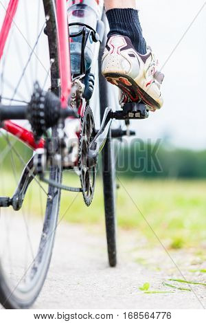 Chain, pedal, rear wheel and sprocket of bike, detail, man having foot on pedal
