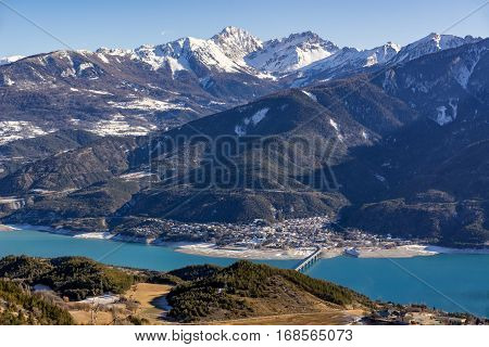 Elevated view over Savines-le-Lac Village and Serre Poncon lake in winter. In the distance the Montagnette and Pouzenc mountain peaks. Hautes-Alpes Southern Alps France