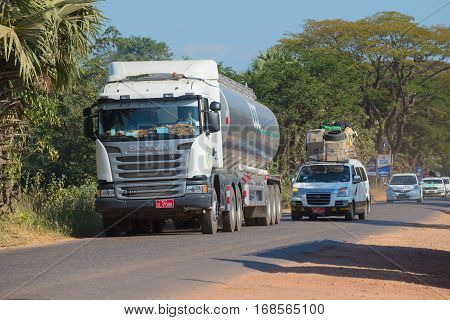KAYIN STATE, MYANMAR - DECEMBER 28, 2016: Minivan overtaking a tanker truck. Traffic on the highway Bago - Myawaddy