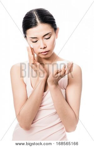 Beautiful young Asian woman applying facial moisturizer cream for sensitive skin care