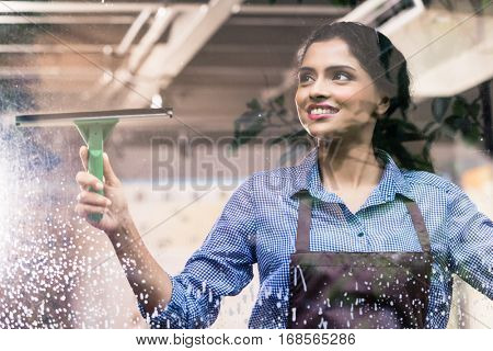 Indian employee cleaning windows with squeegee