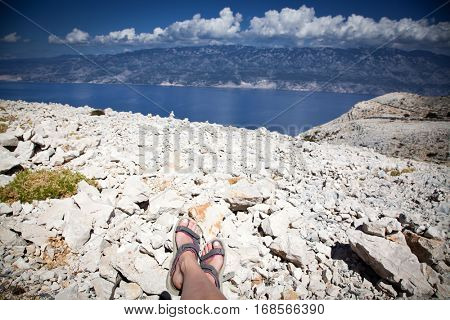 woman's feet in trekking sandals having a view over the sea and the mainland from the highest peak of Rab island, Croatia