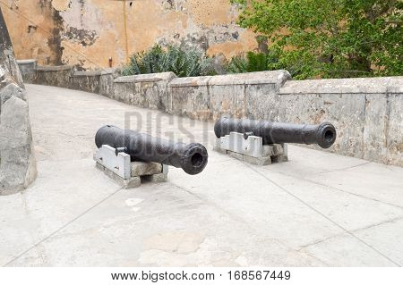 Old cast iron guns in front of the entrance to the Mombasa fortress in Kenya