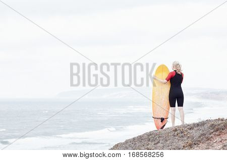 Young blonde woman wearing shorty wetsuit, standing on beach with surfboard in her hands, reading waves and preparing for surfing session - water sports concept. Baleal, Peniche, Portugal