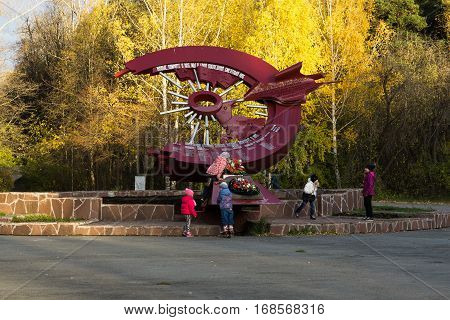 Yekaterinburg, Russia - October 09, 2016: Children at the monument to the scouts motorcyclists Urals Volunteer Tank Corps