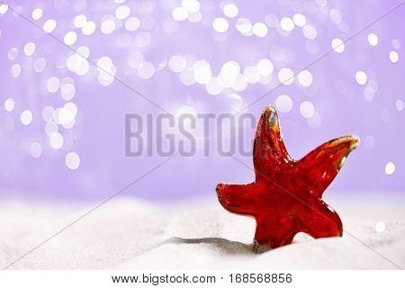 red Glass star fish on beach sand and festive glitter background