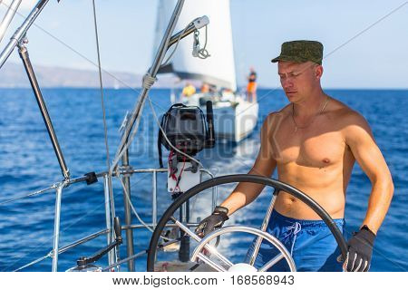 Man at the helm sail boat, the ship controls during sea yacht race.
