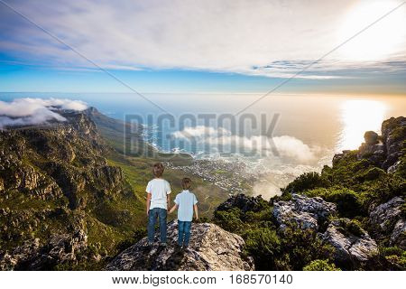 The concept of active tourism and recreation. Two boys standing on top of Table Mountain in the clouds. Travel to Africa