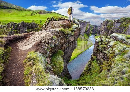 The elderly woman - tourist enthusiastically photographing scenic landscape.  The concept of active northern tourism. The striking canyon in Iceland. Green Tundra in summer