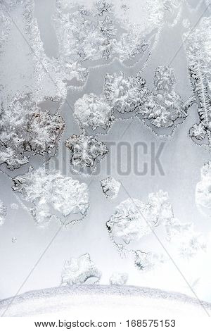 Beautiful hoarfrost tracery on frozen window a frosty day indoor vertical view closeup