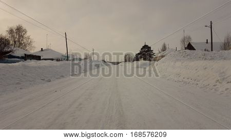 A day in Russian village in winter time. The road to other end of the village with a lot of snow on roadsides