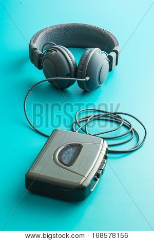 The vintage audio player and headphones on blue background.