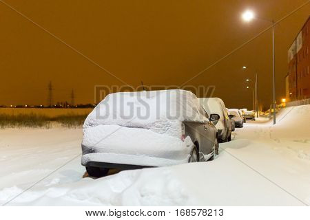 Snowy street with cars after winter snowfall in Poland