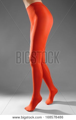 Beautiful woman legs in color tights on grey background