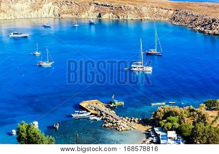 Beautiful small closed port of St. Paul beneath the rocks of Acropolis of Lindos with its blue waters and white boats, Rhodes Island, Greece