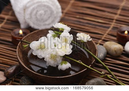 White Cherry flower on bowl with pile stones ,towel on mat