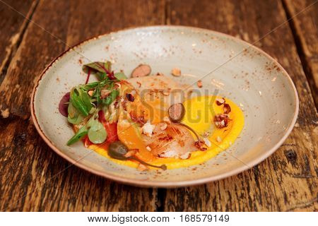 Calamari and citrus sauce starter with orange slices and pumpkin mash on old wooden table