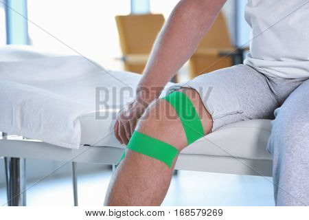 Physiotherapist applying kinesio tape onto patient's knee in clinic, closeup