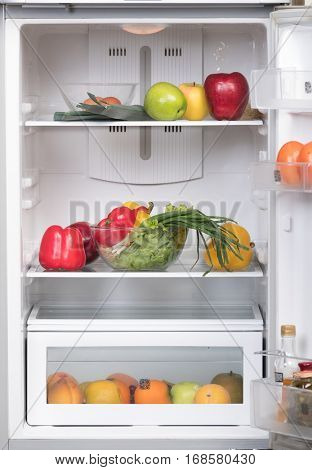Open fridge with fruits and vegetables on the shelves