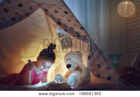 Cute little child is reading a book with flashlights in tent. Happy girl plays at home. Funny lovely kid having fun in children room.