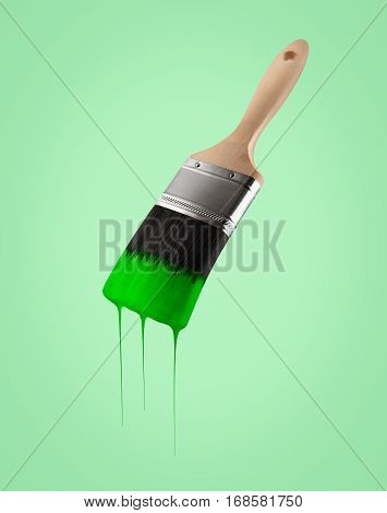 Paintbrush loaded with green color dripping off the bristles on gree background.