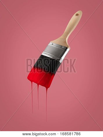Paintbrush loaded with red color dripping off the bristles on red background.